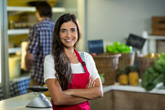 Smiling woman vendor standing at the counter in grocery store with arms crossed Royalty Free Stock Photography