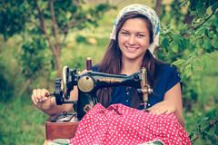 Smiling woman with vintage hand sewing machine Stock Images