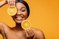 Smiling woman with vivid makeup and orange. Smiling african woman with vivid makeup and orange slices in hand. Happy female model with healthy skin over yellow Royalty Free Stock Photography
