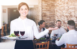 Smiling woman waiter carrying order for visitors Stock Image