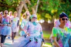 Smiling Woman Smiling Walking In Color Frenzy Fun Run. MACKAY, QUEENSLAND, AUSTRALIA - JUNE 2019: Unidentified woman smiles as she walks in Color Frenzy Fun Run stock photo