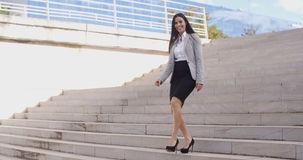 Smiling woman walking down staircase Royalty Free Stock Photography
