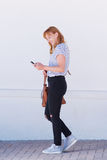 Smiling woman walking with mobile phone and bag Stock Photo