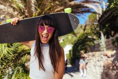 Smiling woman walking outdoors holding skateboard. Excited female with sunglasses and skateboard looking at camera and laughing Stock Images