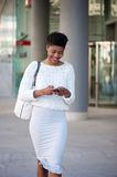Smiling woman walking on sidewalk and sending text message Stock Images