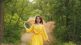 Smiling woman walking with smoke bomb in forest