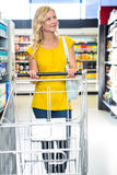 Smiling woman walking with trolley Royalty Free Stock Images