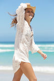 Smiling woman walking in white summer dress at the beach Stock Image