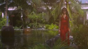 Smiling Woman Walks near Fountain in Tropical Garden. Smiling woman in long dress walks near decorated fountain against white building in tropical garden stock video footage