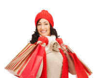Smiling woman in warm clothers with shopping bags Stock Photo