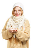 Smiling woman in warm clothing holds snow Royalty Free Stock Images