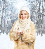 Smiling woman in warm clothing holds snow Stock Images