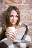 Smiling woman in warm plaid holding cup with hot coffee Stock Photography