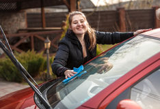 Smiling woman washing car windscreen at yard Stock Photography