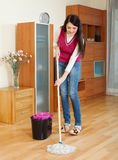 Smiling  woman washing  floor with mop Royalty Free Stock Photo