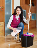 Smiling  woman washing  floor with mop and detergent Royalty Free Stock Photography