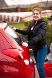 Smiling woman washing red car at backyard Stock Photo