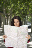 Smiling woman watching a map Royalty Free Stock Photos