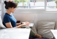Smiling woman watching video on laptop computer in cozy coworking interior, female student rest during free time reading news blog royalty free stock image