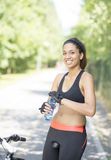 Smiling woman with water bottle after exercising with bike Stock Photo