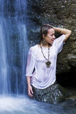 Smiling woman in waterfall. Young woman under blue waterfall Stock Image
