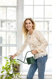 Smiling woman watering plant at home Royalty Free Stock Images