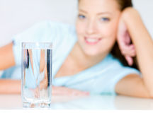 Smiling woman  with  waters glass Royalty Free Stock Photography