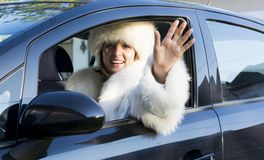 Smiling woman waving from a car window Stock Photo