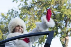 Smiling woman waving from a car window Royalty Free Stock Image