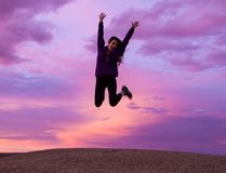 Smiling Woman Wearing Black Jacket and Pants Jumping in Brown Open Field Stock Photography