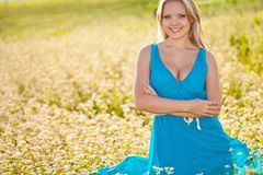 Smiling woman wearing blue dress on a field Stock Photos
