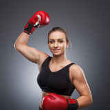 Smiling woman wearing boxing gloves Stock Images