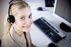 Smiling woman wearing a call centre headset Stock Photography