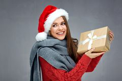 Smiling woman wearing christmas hat holding paper gift box and l. Ooking side. Gray wall back Stock Photos
