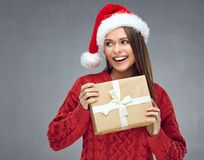 Smiling woman wearing christmas hat holding paper gift box and l. Ooking side. Gray wall back Royalty Free Stock Photos