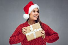 Smiling woman wearing christmas hat holding paper gift box and l. Ooking side. Gray wall back Royalty Free Stock Image