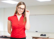 Smiling woman wearing eyeglasses in a classroom Stock Photo