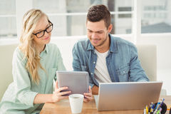 Smiling woman wearing eyeglasses showing digital tablet to man. Smiling women wearing eyeglasses showing digital tablet to men while sitting at desk Stock Photography