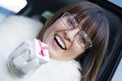 Smiling woman wearing glasses holding a gift box Stock Photos