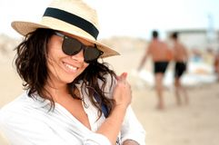 Smiling woman wearing hat and glasses on private beach at resort Royalty Free Stock Photo