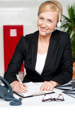 Smiling woman wearing headset writing on notepad Stock Image