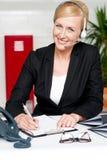 Smiling woman wearing headset writing on notepad Stock Image