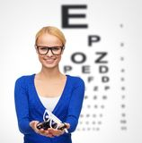 Smiling woman wearing and holding eyeglasses Royalty Free Stock Image