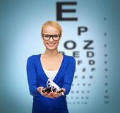 Smiling woman wearing and holding eyeglasses Stock Photos