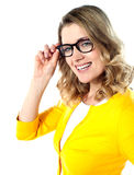 Smiling woman wearing and holding her glasses Royalty Free Stock Photography