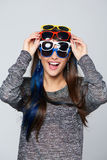 Smiling woman wearing many colourful sunglasses Royalty Free Stock Photos