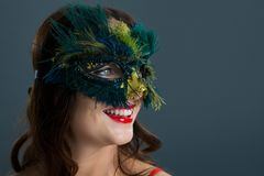 Woman wearing masquerade mask against black background. Smiling woman wearing masquerade mask against black background Royalty Free Stock Photo