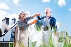 Free Smiling Woman Wearing Peaked Cap Joining Her Husband Watering Plants Royalty Free Stock Images - 129188239