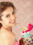 Smiling woman, wearing a pink suitcase, holding a tasty blue milk shake in a jar, with a heart candy, plastic straw on a Royalty Free Stock Photography