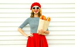 Smiling woman wearing red beret holding paper bag with long white bread baguette. Portrait pretty smiling woman wearing red beret holding paper bag with long royalty free stock photo